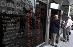 Мужчина выходит из пункта обмена валют в Буэнос-Айресе, 8 ноября 2011 года. Единая европейская валюта снижается в понедельник утром после роста, вызванного назначением в воскресенье вечером нового премьер-министра Италии, так как инвесторы заняли выжидательную позицию и хотят посмотреть, насколько легко Риму сегодня удастся разместить 5- летние долговые бумаги. REUTERS/Marcos Brindicci