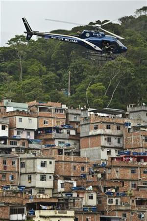 A police helicopter flies over Rocinha slum during the ''Shock of Peace'' operation to install a Peacekeeping Unit (UPP) in Rio de Janeiro November 13, 2011. REUTERS/Marcos Michael