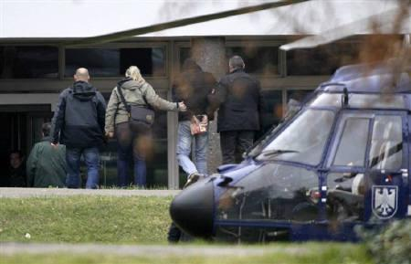 A suspected accomplice of a neo-Nazi cell, with his hands cuffed (2nd R) is escorted by police after arriving by helicopter at Germany's federal state prosecutor at the Bundesgerichtshof in Karlsruhe November 14, 2011. REUTERS/Wolfgang Rattay