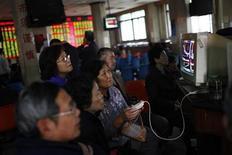 Инвесторы следят за изменениями фондовых котировок в брокерском доме в Шанхае 10 ноября 2011 года. Акции в Азии подешевели во вторник во главе с финансовым сектором на фоне снижения аппетита инвесторов к риску после того, как Италия в понедельник заплатила рекордную цену за размещение 5-летних долговых бумаг, что стало причиной роста доходности других облигаций. REUTERS/Aly Song