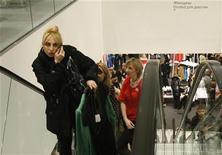 Женщина разговаривает по телефону в магазине Hennes & Mauritz (H&M) в Москве 13 марта 2009 года. Российский оператор мобильной связи Мегафон снизил чистую прибыль в третьем квартале 2011 года на 10,9 процента в годовом выражении до 12,5 миллиарда рублей, сообщила компания во вторник. REUTERS/Denis Sinyakov