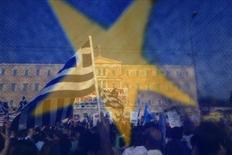 Участники демонстрации перед зданием парламента в Афинах видны сквозь флаг ЕС. Греция должна дать европейским партнерам письменное обязательство проводить реформы ради сокращения госдолга вне зависимости от того, кто выиграет выборы, заявила во вторник Европейская комиссия. Фотография сделана 5 июня 2011 года.