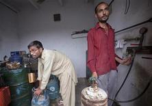 Рабочие в Карачи наполняют баллоны сжиженным газом 3 ноября 2011. Туркмения согласовала с Пакистаном цену газа, который Ашхабад планирует поставлять по непостроенному пока газопроводу Туркмения-Афганистан-Пакистан-Индия (TAPI), сообщили Рейтер два источника в туркменском правительстве Туркмении. REUTERS/Akhtar Soomro