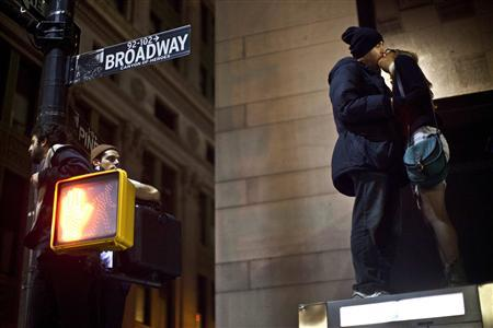 Protesters affiliated with the Occupy Wall Street movement kiss while standing on top of a bus stop during an unannounced raid by the New York City Police Department outside Zuccotti Park in New York, in the early hours of November 15, 2011.  REUTERS/Andrew Burton