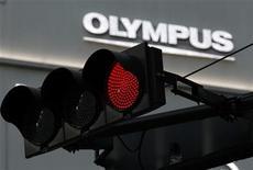 Логотип компании Olympus виднеется за светофором в Токио, 17 ноября 2011 года. Японские правоохранительные органы собираются допросить экс-президента Olympus Corp в связи с нарушениями в бухгалтерии производителя фотоаппаратов и медицинского оборудования, расследуя возможные связи компании с организованной преступностью. REUTERS/Kim Kyung-Hoon
