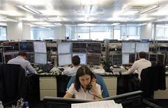 Трейдеры следят за ходом торгов в торговом зале инвестиционного банка в Москве, 9 августа 2011 года. Российские фондовые индексы после короткого перерыва накануне вернулись к снижению при открытии рынка в среду, подхватив движение на зарубежных площадках. REUTERS/Denis Sinyakov
