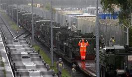 """Немецкие железнодорожные рабочие следят за погрузкой БТР """"Страйкер"""", состоящих на вооружении 2-го бронекавалерийского полка армии США, в Графенворе. Фотография сделана 12 июля 2007 года. The unit will be deployed to Iraq for a 15-month assignment starting in early August 2007. США прекратят обмен данными с Россией в рамках договора ДОВСЕ, который ограничивает вооруженные силы в Европе, заявив, что делают это через четыре года после того, как Москва приостановила участие в пакте. REUTERS/Michael Dalder"""