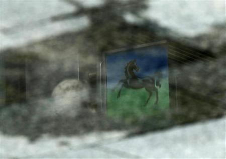 A sign of a branch of Lloyds is reflected in a puddle, in London May 5, 2011.  REUTERS/Luke MacGregor