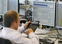 Трейдер работает в торговом зале инвестиционного банка в Москве, 9 августа 2011 года. Российские фондовые индексы после короткого снижения при открытии в четверг начали расти вслед за ценами на нефть. REUTERS/Denis Sinyakov