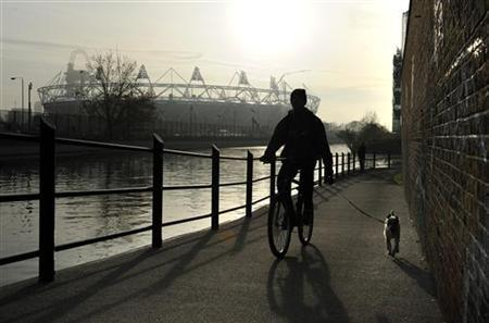 A man cycles with his dog along a canal, near the Olympic stadium in east London November 23, 2011.    REUTERS/Paul Hackett