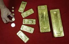 Сотрудник Bank of Taiwan раскладывает на столе золотые монеты и слитки в Тайбэе 7 октября 2009 года. Цены на золото снижаются под давлением роста доллара и из-за отсутствия согласия среди лидеров Европы о мерах борьбы с долговым кризисом. REUTERS/Pichi Chuang