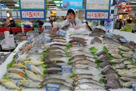 A shop assistant arranges fish for sale at a supermarket in Hangzhou, Zhejiang province January 14, 2011.  REUTERS/Steven Shi