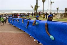 """People participate in the """"Walk the Future"""" event through the streets of Durban November 27, 2011. According to organizers the walk along The Blue Line, a blue line painted on the ground by artist Strijdom van der Merwe, highlights rising sea levels and the challenge of climate change. It is led by The Premier of KwaZulu Natal, Dr Zweli Mkhize. REUTERS/Rogan Ward"""