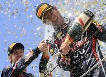 Campeão da Fórmula 1 pela Red Bull, Sebastian Vettel (esq), com champagne no pódio ao lado do colega de equipe Mark Webber, no Grande Prêmio do Brasil em Interlagos, São Paulo, no domingo. A Red Bull negou suspeitas de que tenha manipulado o Grande Prêmio do Brasil, no domingo, para dar ao australiano Mark Webber sua primeira e única vitória na temporada 2011 da Fórmula 1. 27/11/2011 REUTERS/Nacho Doce