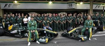Piloto da Lotus Heikki Kovalainen (dir) e seu colega de equipe Jarno Trulli posam para foto colegiva antes do Grande Prêmio do Brasil, em Interlagos. Terminar em 10o lugar no Mundial de Fórmula 1 este ano pode elevar o orçamento da equipe Caterham em 28 milhões de dólares na próxima temporada, de acordo com o chefe da equipe, Tony Fernandes.  27/11/2011 REUTERS/Ricardo Moraes