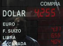 Человек смотрит на электронное табло с текущим курсом валют в пункте обмена валюты в Буэнос-Айресе, 23 ноября 2011 г. Евро растет к доллару во вторник, так как инвесторов обрадовало, что Италии удалось продать гособлигации на рынке, даже несмотря на то, что ей пришлось заплатить за это рекордную доходность. REUTERS/Marcos Brindicci