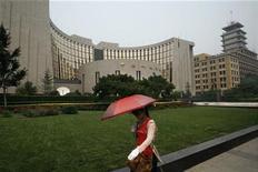 Женщина идет мимо Народного банка Китая в Пекине, 28 июня 2010 г. Единая европейская валюта, европейские акции и фьючерсы на американские фондовые индексы резко выросли в среду на фоне скачка оптимизма у инвесторов, спровоцированного неожиданным снижением банковских резервных требований Китаем. REUTERS/Bobby Yip