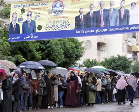 Women holding umbrellas and covering themselves stand in line during rain under an election poster by Egypt's Muslim Brotherhood ''The Freedom and Justice Party''' outside a polling station as they wait to cast their votes during parliamentary elections in Alexandria, November 28, 2011. REUTERS/Mohamed Abd El-Ghany