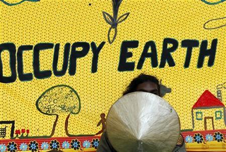 A protester gestures in front of a banner outside the COP17 (Conference of the Parties of the United Nations Climate Change) venue in Durban November 28, 2011. REUTERS/Siphiwe Sibeko