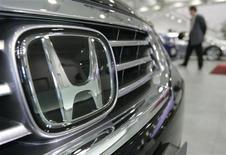 Мужчина смотрит автомобили Honda Motor Co. в Токио, 30 января 2008 года. Honda Motor Co сообщила об отзыве 304.035 автомобилей по всему миру из-за неполадок в работе воздушных подушек безопасности. REUTERS/Michael Caronna