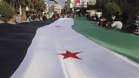 12月5日、反政府デモへの弾圧が続くシリアの活動家は4日にトルコとの国境に近いシリア北西部イドリブの空軍情報機関から秘密警察隊員10数人が離反したと明らかにした。写真は1961―63年の国旗を掲げて抗議するデモ参加者。2日撮影。提供写真(2011年 ロイター)