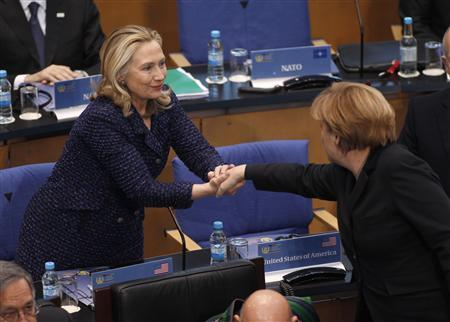 U.S. Secretary of State Hillary Clinton shakes hands with German Chancellor Angela Merkel (R) during the conference on Afghanistan at the former German parliament in Bonn December 5, 2011.    REUTERS/Ina Fassbender