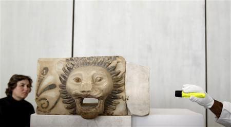 A monument conservator lights a lion head-spout during a media tour at the Acropolis museum in Athens, December 5, 2011. REUTERS/Yiorgos Karahalis