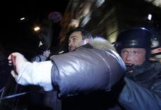 Полиция задерживает демонстранта на Триумфальной площади в Москве 6 декабря 2011 года. Сотни демонстрантов во вторник вечером вышли в центр российской столицы, продолжив начавшиеся накануне самые массовые акции протеста против правления Владимира Путина в последние годы. REUTERS/Anton Golubev