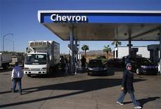 Люди проходят мимо заправки Chevron в Аризоне, 27 октября 2011 года. Американская нефтяная компания Chevron Corp увеличит расходы примерно на шестую часть в 2012 году, предусматривая крупные инвестиции в глубоководные проекты и два проекта по сжижению природного газа (СПГ) в Австралии. REUTERS/Joshua Lott