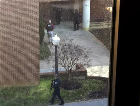 Armed police officers search the area around the Squires Student Center on the Virginia Tech campus for a gunman after a police officer and another person were shot and killed at the university in Blacksburg, Virginia, December 8, 2011. REUTERS/Katherine Davison