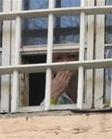 Бывшая премьер-министр Украины Юлия Тимошенко выглядывает из окна тюремной камеры в Киеве, 4 ноября 2011 года. Районный суд Киева явился в камеру к лидеру оппозиции Юлии Тимошенко, отбывающей срок за газовую сделку с Россией, и вынес постановление об ее аресте за плохое поведение, сообщили адвокаты. REUTERS/Yulia Tymoshenko Press Service/Handout