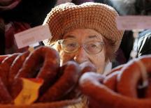 """Пожилая женщина в очереди за мясом на уличном рынке в Минске 5 ноября 2011. Правительство Белоруссии в пятницу вдвое расширило перечень """"социально-значимых товаров"""", цены на которые будут регулироваться властями, чтобы обуздать превысившую 100 процентов инфляцию. REUTERS/Vasily Fedosenko"""