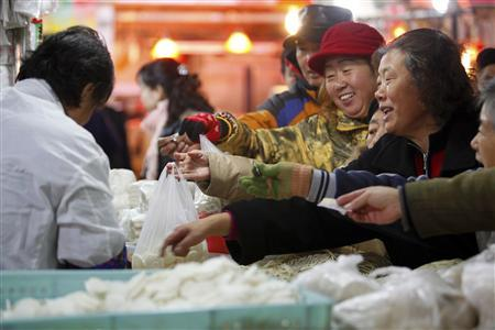 Customers purchase noodles at a stall inside a market in Shanghai December 9, 2011.  REUTERS/Aly Song