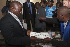 Incumbent Congolese President Joseph Kabila receives his ballot at a polling station in Democratic Republic of Congo's capital Kinshasa, November 28, 2011. REUTERS/Finbarr O'Reilly