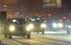 Машины в сильный снегопад в Москве 10 декабря 2010 года. Рабочая неделя в Москве обещает быть ненастной - немного потеплеет, но каждый день будут идти осадки, ожидают синоптики. REUTERS/Nikolay Korchekov