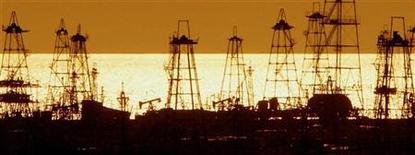 Буровые вышки на рассвете в Баку 16 октября 2005 года. Выбор маршрута экспорта азербайджанского газа в Европу может затянуться до конца первого квартала 2012 года, сообщил журналистам глава госнефтекомпании Азербайджана (ГНКАР) Ровнаг Абдуллаев. REUTERS/David Mdzinarishvili