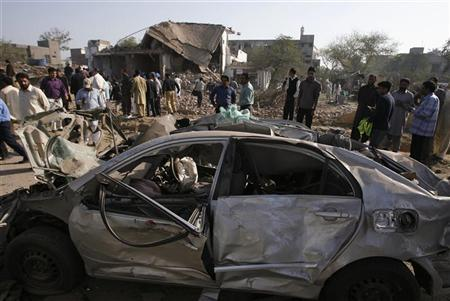 A destroyed car is seen in front of the site of a suicide bomb attack which targeted the Federal Investigation Agency in Lahore March 8, 2010.  REUTERS/Mohsin Raza