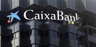 Рабочие убирают тент с нового логотипа CaixaBank на здании его штаб-квартиры в Барселоне 30 июня 2011 года. Агентство Moody's поместило в список на пересмотр с негативным прогнозом рейтинги CaixaBank, Banco Sabadell, Bankia и других испанских банков поздно вечером в понедельник, сославшись на их сильную зависимость от рынка недвижимости и низкую доходность. REUTERS/Albert Gea