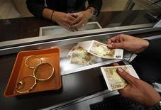 Работник ломбарда в Ницце отсчитывает деньги 24 ноября 2011 года. Греческие власти опубликовали во вторник свод инструкций для граждан, объясняющий, как избежать надувательства при сдаче в ломбард семейного золота и серебра. REUTERS/Eric Gaillard