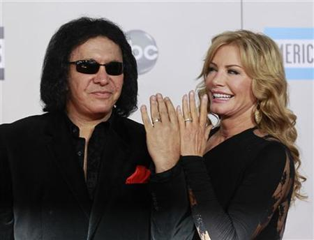 KISS band member Gene Simmons and wife Shannon Tweed show their wedding rings as they arrive at the 2011 American Music Awards in Los Angeles November 20, 2011. REUTERS/Danny Moloshok
