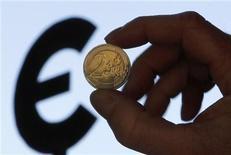 Монета достоинством 2 евро на фоне символа европейской валюты. Фотография сделана 28 ноября 2011 года. Евро в среду колеблется около 11-месячного минимума к доллару и приближается к опционному барьеру, провалившись ниже которого, может начать падать еще быстрее. REUTERS/Francois Lenoir