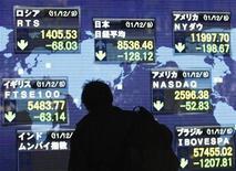 Мужчина смотрит на электронное табло, отображающее котировки главных мировых индексов, возле брокерской конторы в Токио 9 декабря 2011 года. Фондовые рынки Азии закрылись в среду снижением, после того как Федеральный резерв США решил не принимать дополнительные меры стимулирования экономики. REUTERS/Issei Kato