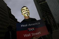<p>An Occupy Phoenix protester, wearing a Guy Fawkes mask, holds a sign during a rally in Phoenix, Arizona December 1, 2011. REUTERS/Joshua Lott</p>