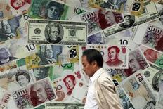Мужчина проходит мимо обменного пункта в Гонконге 26 июля 2011 года. Приток прямых иностранных инвестиций в Китай в ноябре сократился на 9,8 процента до $8,8 миллиарда в годовом исчислении, предвещая сильное замедление экономики страны. REUTERS/Tyrone Siu