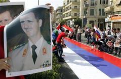 Сторонники президента Сирии Башара аль-Асада расстелили большой российский флаг во время митинга в Дамаске 12 октября 2011 года. Россия предложила Совету безопасности ООН новый, более жесткий проект резолюции в отношении кровопролития в Сирии, усилив надежды Запада на то, что ООН все-таки предпримет какие-то шаги, чтобы повлиять на ситуацию в ближневосточной стране. REUTERS/ Khaled al-Hariri