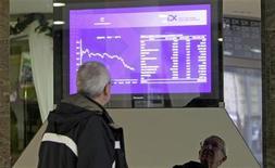Мужчина смотрит на экран на Пражской фондовой бирже, 14 декабря 2011 г. Европейские рынки акций немного подросли в ходе вялых торгов пятницы за счет удорожания металлов, поддержавшего горнорудные акции, а также на фоне данных из США, указавших на восстановление крупнейшей экономики мира. REUTERS/David W Cerny