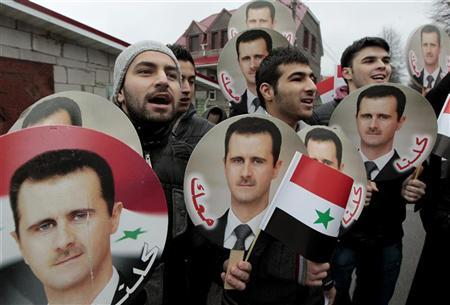 Syrian citizens take part in a rally in support of President Bashar al-Assad in front of the Syrian embassy in Minsk December 17, 2011. About 20 people took part in the rally as a counteract against a protest in solidarity with Syria's anti-government protesters.  REUTERS/Vasily Fedosenko