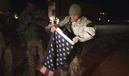 A soldier with the 3rd Brigade Combat Team, 1st Cavalry Division folds up a U.S. flag outside their Mine Resistant Ambush Protected (MRAP) vehicle before leaving Camp Adder to travel with the last U.S. military convoy to leave Iraq December 18, 2011. REUTERS/Lucas Jackson