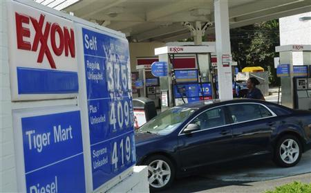 A motorist fills up her car at an Exxon gas station in Arlington, Virginia, August 10, 2011.   REUTERS/Jason Reed
