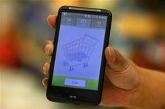 Покупатель показывает мобильное приложение для считывания штрих-кода в магазине в штате Массачусетс, 17 октября 2011 года. Расходы американцев на покупки через интернет в текущем праздничном сезоне выросли на 15 процентов в годовом выражении до $30,9 миллиарда, так как клиенты смогли воспользоваться разными полезными опциями вроде бесплатной доставки, сообщает comScore. REUTERS/Adam Hunger